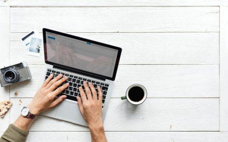 Dłonie piszące na klawiaturze laptopa i kubek czarnej kawy