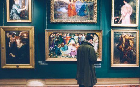 Mężczyzna ogląda obrazy na wystawie
