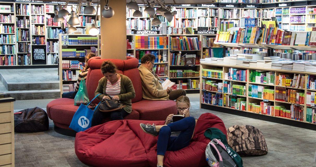 Ludzie w bibliotece lub czytelni czytający książki po angielsku