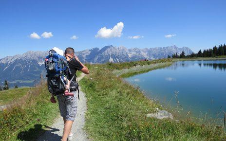 Mężczyzna z dzieckiem w nosidełku turystycznym na szlaku w górach