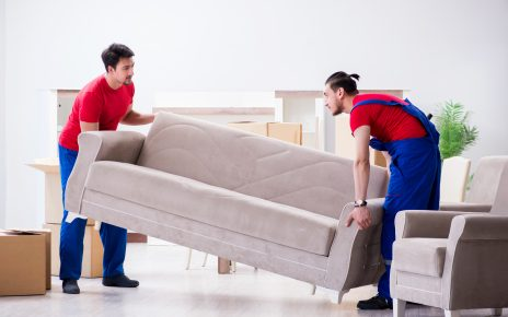 Dwóch mężczyzn podnoszących kanapę