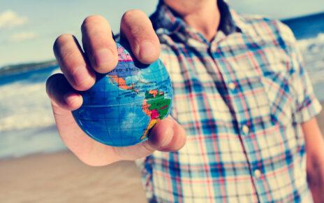 Mężczyzna trzymający w dłoni mały globus