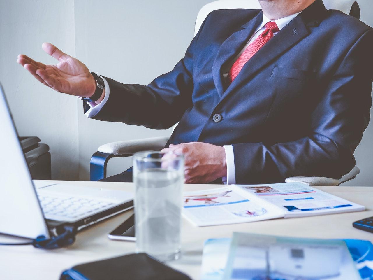 mężczyzna w garniturze siedzi przy biurku z dokumentami i otwartym laptopem, obok stoi szklanka z wodą