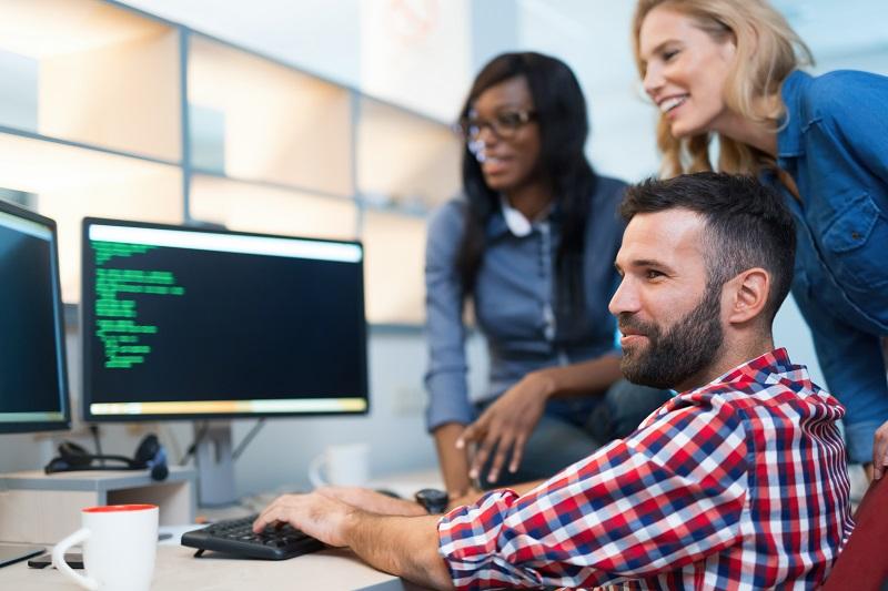 programiści przed komputerem sprawdzają nowe oprogramowanie.