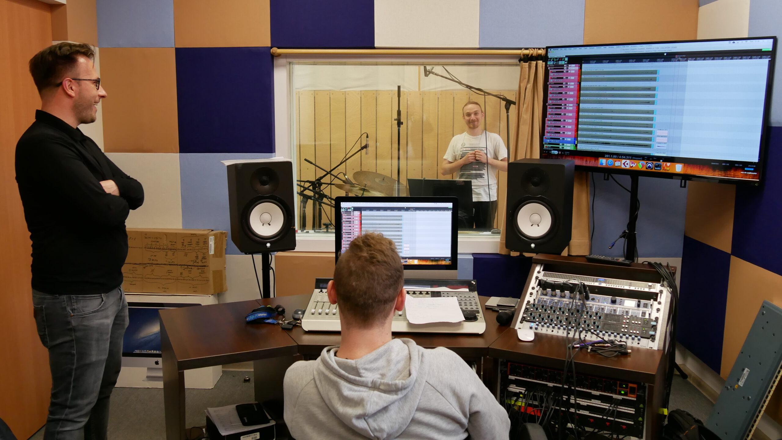 ludzie w studiu nagraniowym, wokół dużo sprzętu, głośniki, mikrofony