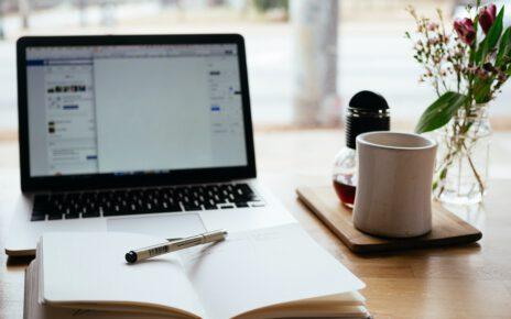 drewniane biurko na którym stoi laptop z kalendarzem i kubkiem
