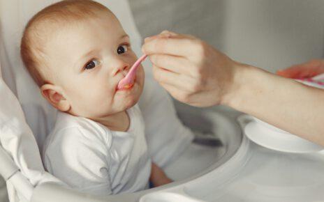 Jedzące dziecko z nietłukącego zastawu stołowego.