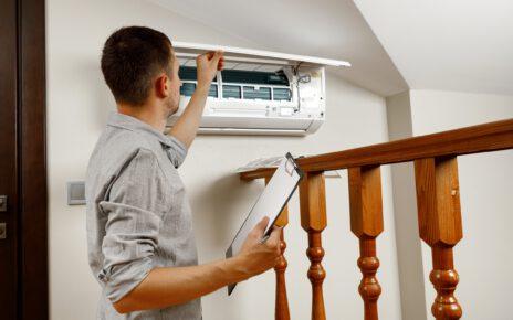 Mężczyzna zakłąda w domu nowoczesną klimatyzację