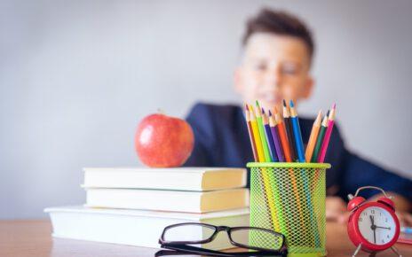 Chłopiec siedzi w ławce szkolnej