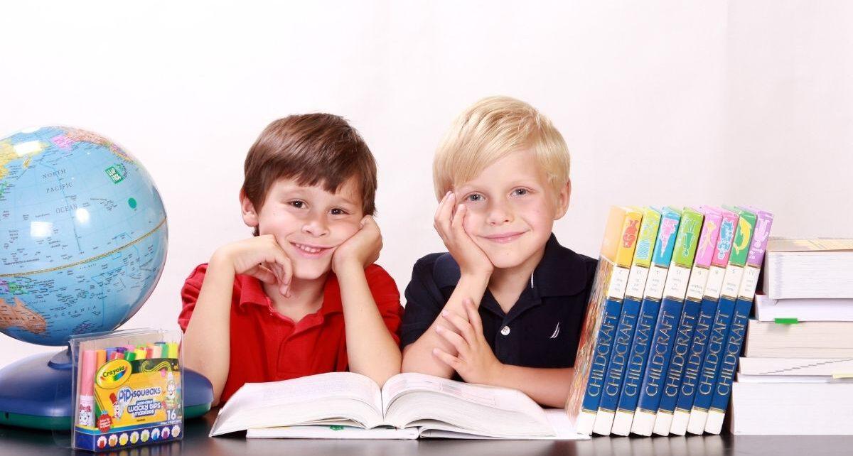 Dwuch chłopców siedzi przy biurku obok wyprawki szkolej